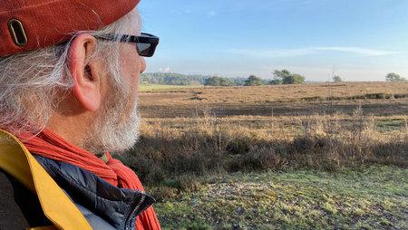Side view on the face of an elderly man looking at a heather landscape in wintertime. Wide landscape Standard-Bild