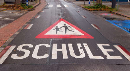 Warning sign for playing children painted on the pavement / asphalt. 'Schule' is German and means school