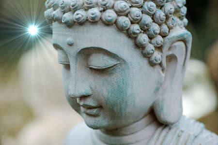 Head of a peaceful meditating buddha. Buddha head in close-up. The statue stands in our garden. In the background is a blurred white buddha statue visible