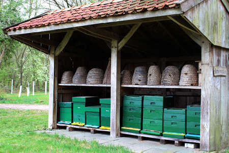 Reconstructed old fashioned bee barn for beekeeping. There are two rows of beehives in. Baskets and boxes. Bee skeps.