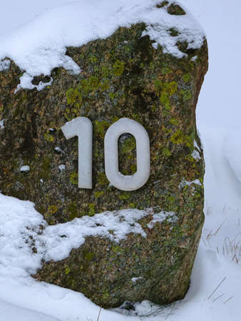 Number ten in white on a stone covered with snow Standard-Bild