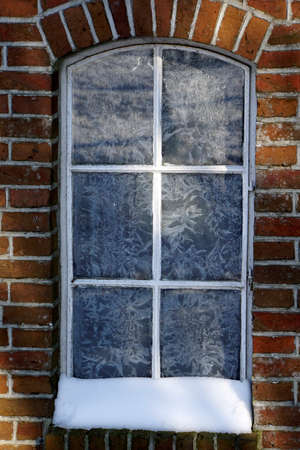 Old window in the winter. Ice crystals on the glass. Brick wall. Hoarfrost. Standard-Bild