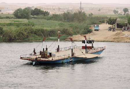 Nile, Egypt - March 28, 2015. An empty car ferry getting passengers. They are waiting to embark at the riverbank. A rudimentary ferry slip is seen on the picture.