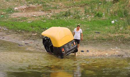 Nile, Egypt - March 28, 2015. An unusual car wash in the Nile. This man appears to be washing his 3wheel black yellow auto rickshaw in the Nile.