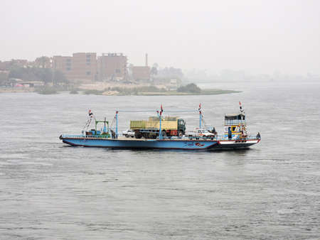 Nile, Egypt - March 28, 2015. An Egyptian ferry getting over the Nile early in the morning. On the ferry are two trucks, cars, mule and some people. In the distance is the vague outline of an Egyptian Editorial