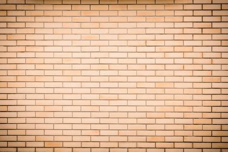 ビネットを背景として現代の鮮やかな黄色のレンガ壁