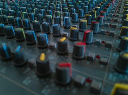 Front panel of old music radio console with colorful potentiometers and sliders Stock Photo