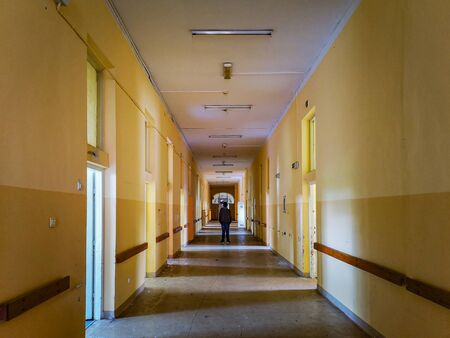Man standing at center of corridor in old abandoned hospital Stock Photo