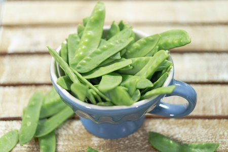 Sugar snap peas on rustic background and blue cup