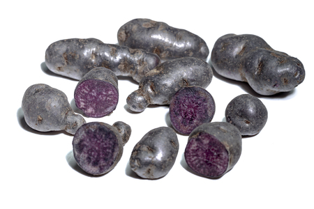 Truffle potato, Vitelotte, Blue-violet potatoes on a white background