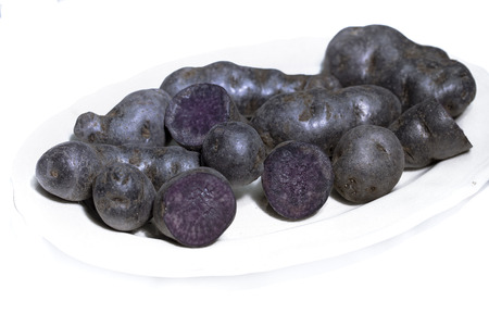 Truffle potato, Vitelotte, Blue-violet potatoes on a white background
