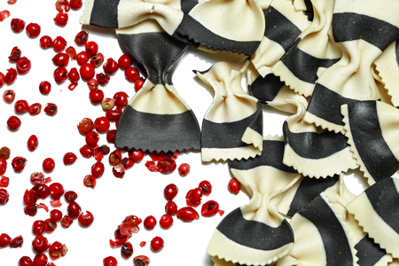 Pasta di semola di grano in white background with red peppercorns
