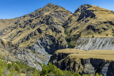 New Zealand South Island - Dumps and tailings from gold mining at Maori Point on Shotover River on Skippers Canyon Road north of Queenstown in the Otago region Standard-Bild - 127443767