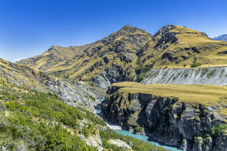 New Zealand South Island - Dumps and tailings from gold mining at Maori Point on Shotover River on Skippers Canyon Road north of Queenstown in the Otago region Standard-Bild - 127443905
