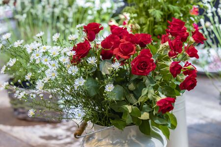 Bouquet with red roses in a white vintage vase with daisies in a white basket Standard-Bild - 127444095