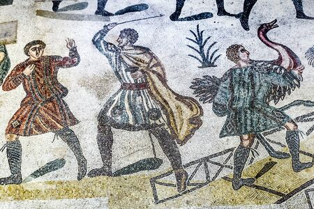 PIAZZA ARMERINA, SICILY, ITALY - May 24, 2018: Ancient Roman mosaics with fighting and hunting scenes in the archaeological site of Villa Romana del Casale - UNESCO World Heritage Site