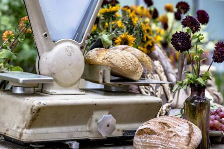Crispy wholemeal bread loaves on a nostalgic scale at a weekly market