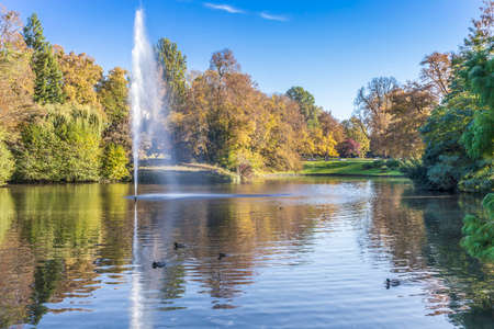 Kurpark pond with autumnal trees and fountain in the Kurpark Wiesbaden