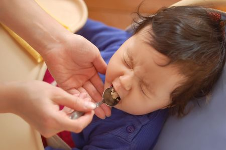 little girl closed her eyes tight as if she doesnt want to eat chicken which her mother gave her on spoon  photo