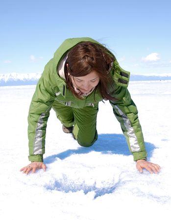 bending over: girl bending over ice hole at Baikal Stock Photo
