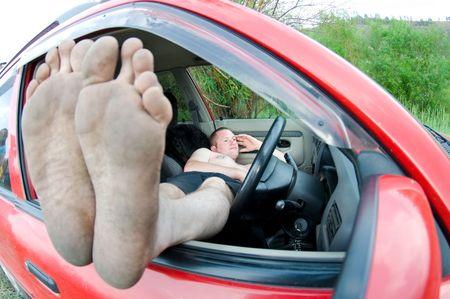 adentro y afuera: hombre en coche piernas en la ventana Foto de archivo