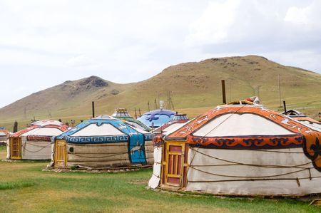 mongolian: several mongolian coloured jurts encamped by hills