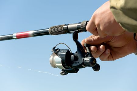 spinning reel: close up shot of a spinning reel in hands