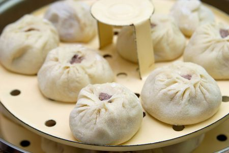 holed: Buuza is one of Buryat (Mongolian) national dishes, paste packets stuffed with minced meat and then they are steamed. They are much similar to chinese dumplings. Stock Photo