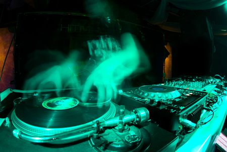 blurred dj at spin table in night club photo