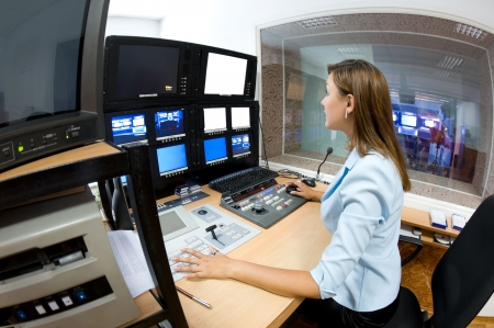 control panel: female TV director at editor in studio