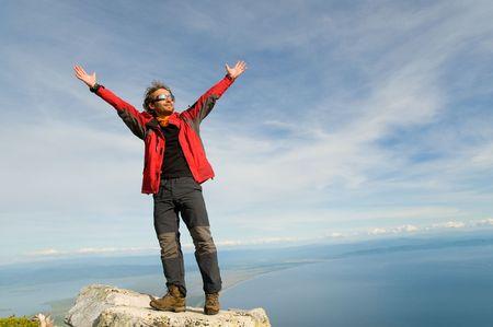 hombre joven se sit�a en la cima de la monta�a regocijo y extendiendo sus brazos amplia hasta  Foto de archivo - 5853579