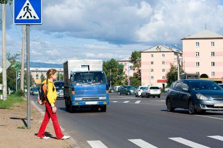 nine year old girl with rucksack walks to crosswalk Stock Photo