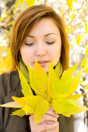young beautiful european girl looks at bunch of autumn leaves in her hands photo