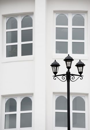 antiqued: antiqued forged black street lamp against white wall with four arched windows