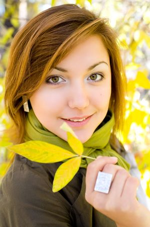 young beautiful european girl holding yellow leaf in autumn forest photo