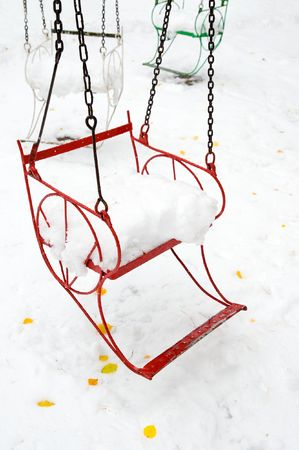 full suspended: empty seat of merry-go-round full of snow