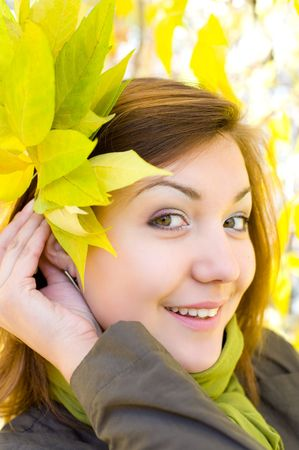 young beautiful european girl with bunch of autumn yellow leaves photo