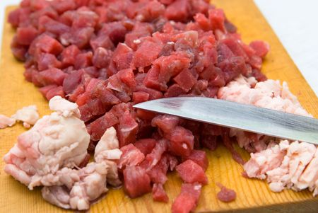 hardboard: cut beef and fat on wooden hardboard with knife blade in shallow DOF Stock Photo