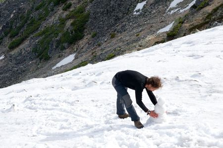 flank: european bowing man models snowman at flank of mountain half covered with snow