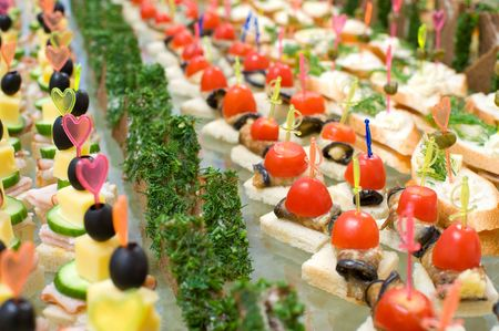 food buffet: a lot of canapes with skewer on buffet table, shallow DOF
