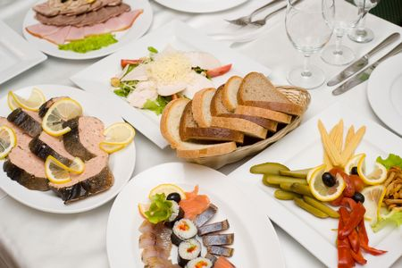 laid table with tableware and cold snacks for banquet in shallow DOF photo