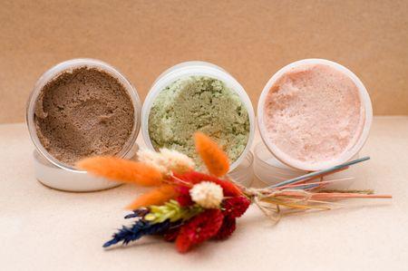 three plastic jars with coloured saline body scrub photo