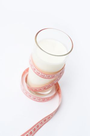 kefir: glass of kefir wound with a measuring tape as concept of cultured milk diet, shallow DOF Stock Photo