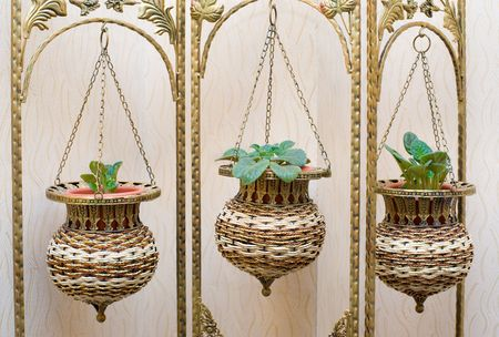 floristics: pot flower stand, forged frame with wicker ornamental flowerpots on chains