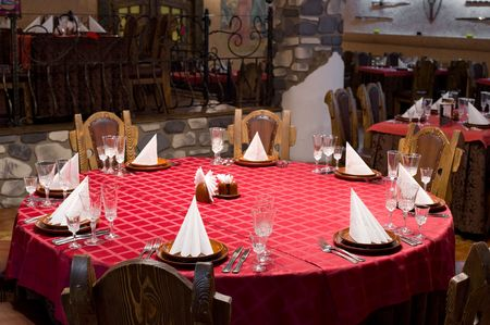 round chairs: round laid table in a restaurant of medieval castle design Stock Photo