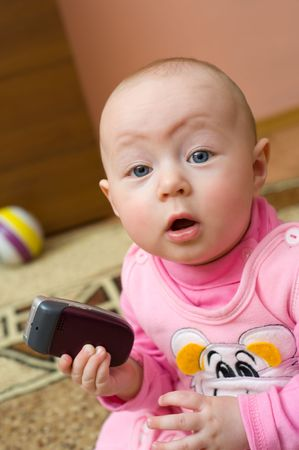 little european surprised eight months old girl holds cell phone and looks into camera photo