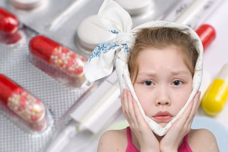 mumps: a girl with a bandage around her face, various pills and a glass thermometer in the background