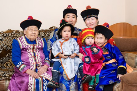 big buryat (mongolian) family: grandmother, grandson with wife and children, in national costumes photo