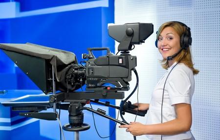 mass media: a female cameraman at a studio smiles into camera