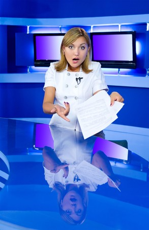 a television anchorwoman at a studio is shocked by news she has in her hands Stock Photo - 7434643